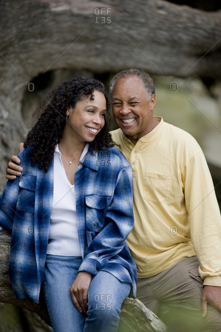 Couple sitting together on tree trunk