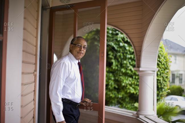 Mature, well-dressed man walks onto his balcony