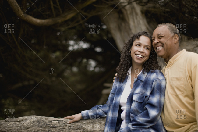 Mature couple smiling and leaning against a tree