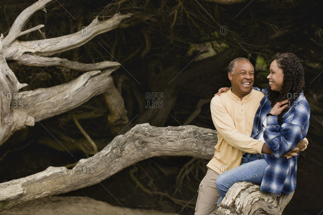 Mature couple smiling and sitting on a branch