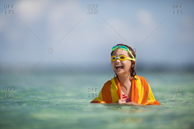 Smiling young girl happily playing in the water while wrapped in a stripy towel.