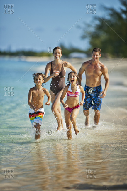 Happy family splashing in shallow water at a tropical beach.