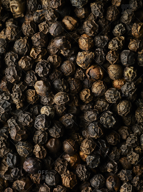 Macro shot of whole black peppercorns fiilling the frame, shot from above.