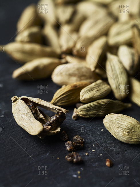 A pile of cardamom pods with one in the foreground, crushed open and seeds flaling out. Others in the background out of focus.