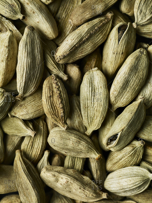 A pile of cardamom pods filling the frame, close-up and shot from above.