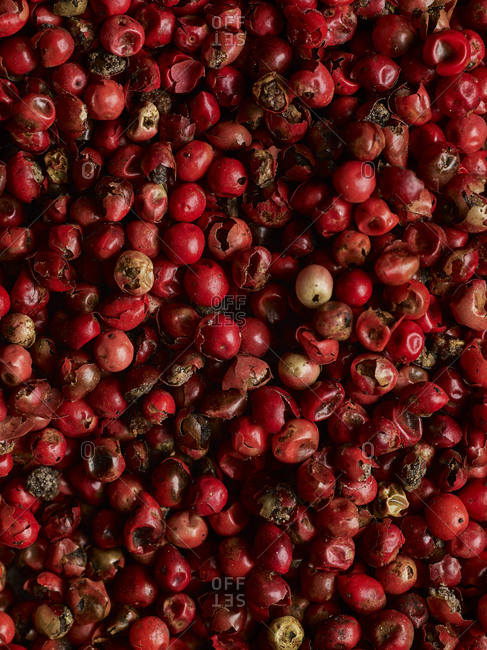 A macro shot of whole and broken pink peppercorns shot from above filling the frame.