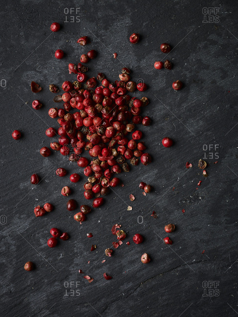 Whole pink peppercorns on a piece of slate shot form above, with some crushed pepper scattered about.