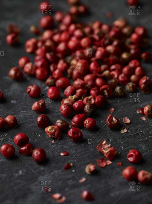 Close-up of some whole pink peppercorns on a piece of slate shot form an angle, with some crushed pepper scattered about.