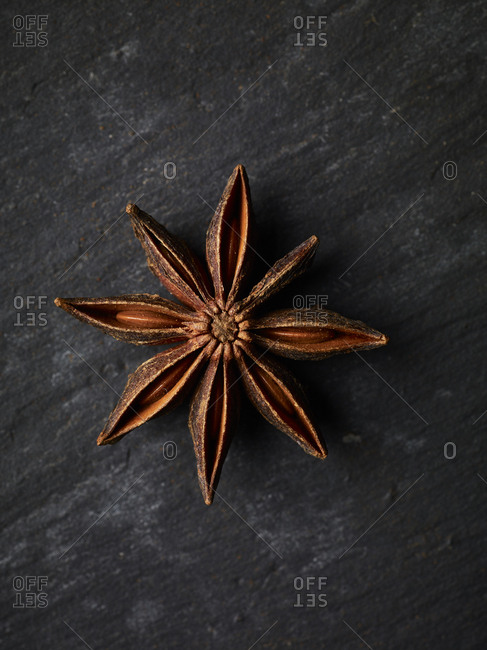 A close up macro shot of one star anise shot from above, showing of the details and structure of the spcie with it's seeds.