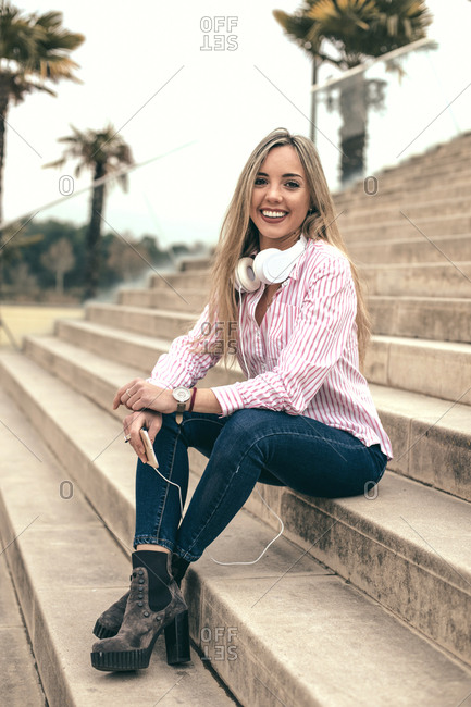 Young blonde woman sitting on steps wearing headphones connected to cell phone