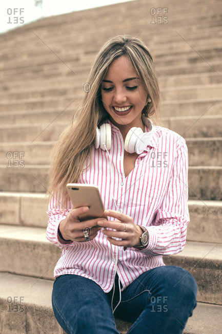 Young blonde woman using cell phone while sitting on steps wearing headphones