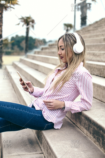 Side view of young blonde woman sitting on steps wearing headphones connected to cell phone