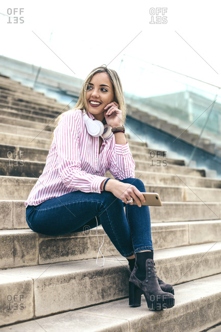 Young blonde woman with cell phone while sitting on steps wearing headphones