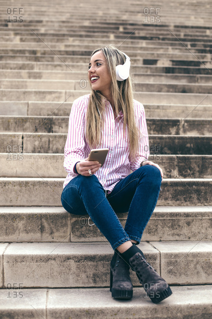 Young blonde woman sitting on steps listening to music on her cell phone