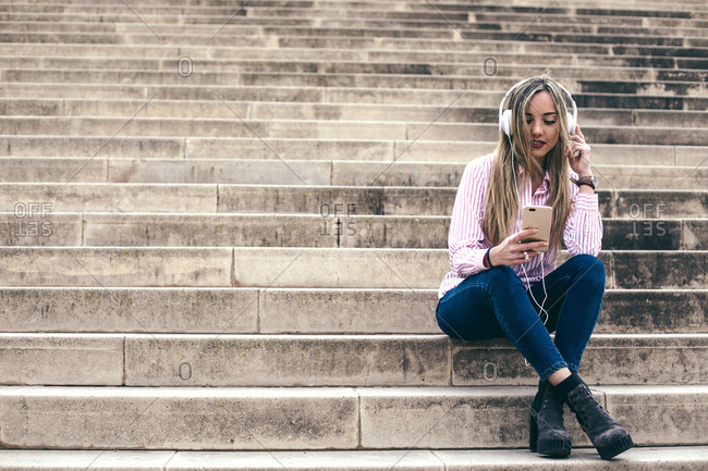 Young blonde woman listening to music on her cell phone on steps