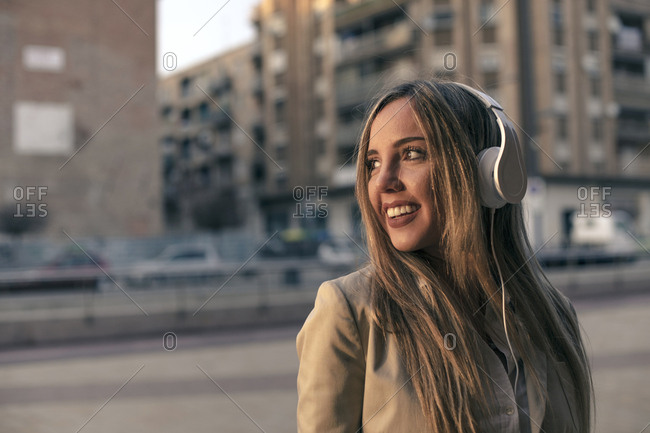Young blonde woman wearing headphones on city street at sunset