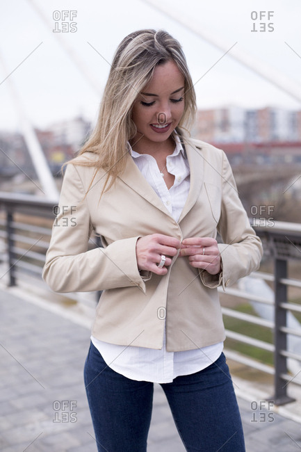 Young blonde woman buttoning her jacket