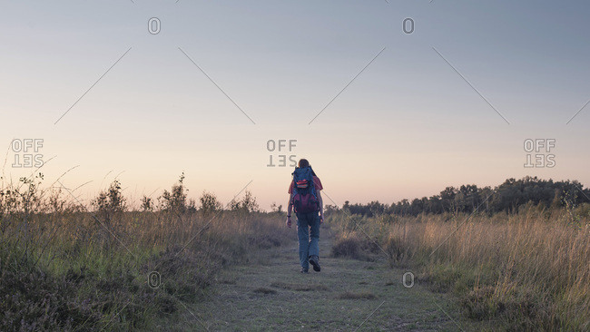 Man hiking with a backpack in a field at sunset