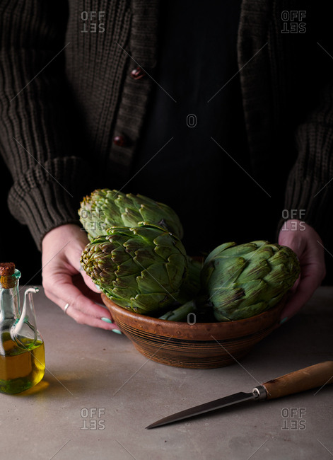 Woman with bowl of artichokes