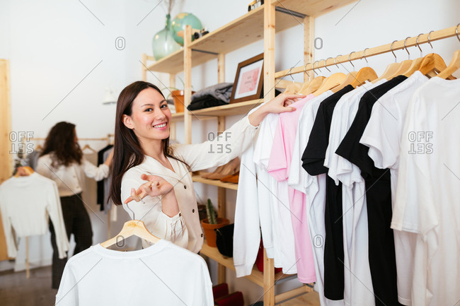 Portrait of young saleswoman standing in clothing store, hanging t-shirts on rail.