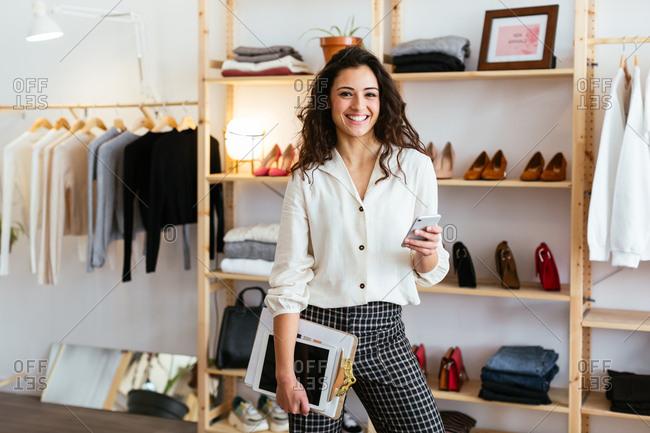 Portrait of confident saleswoman holding phone at store.