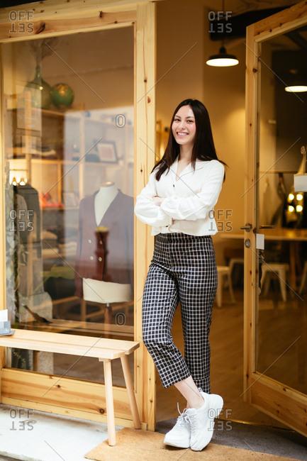 Portrait of saleswoman standing at doorway in store.