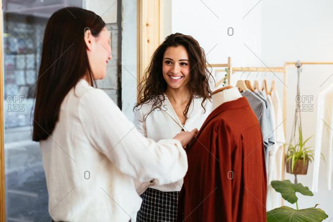 Smiling saleswomen working at store.