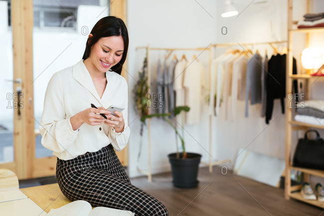 Saleswoman using phone at store.