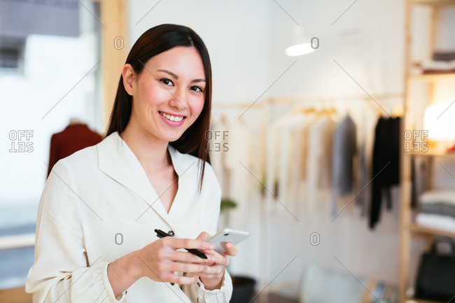 Portrait of saleswoman using phone at store.
