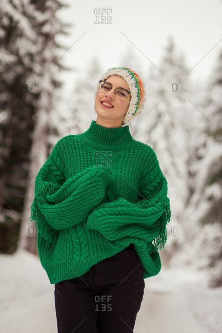 Woman posing in snowing forest in wide knit sweater