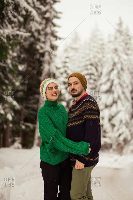 Woman and man posing outside in woods