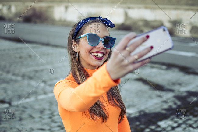 Young woman with sunglasses smiling while taking a selfie with her mobile phone
