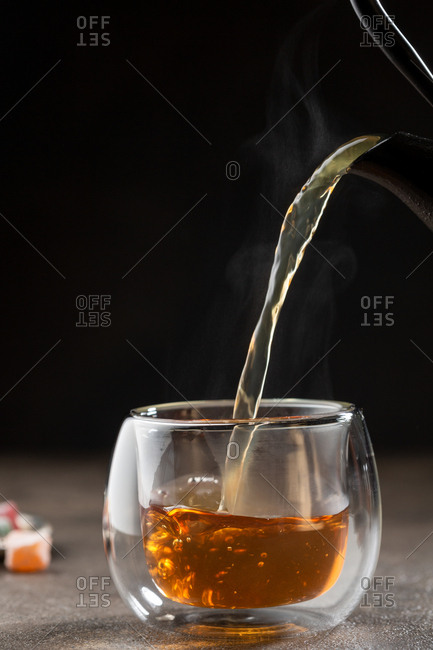 Pouring hot tea in glass cup