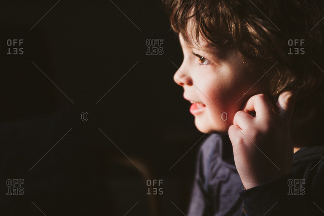 Close up portrait of a little boy smiling's face in the light