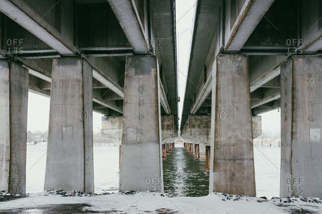 Snowy ground and cold river under freeway