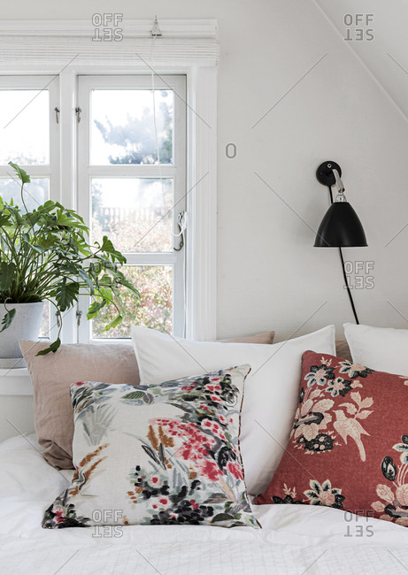 Bed with throw pillows lamp and window