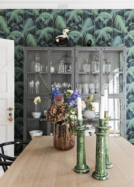Vertical shot of wooden dining table with candlesticks and flowers cupboard and wallpaper