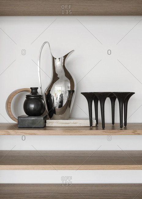 Vertical shot of pitcher, jars and candle stick on shelves.