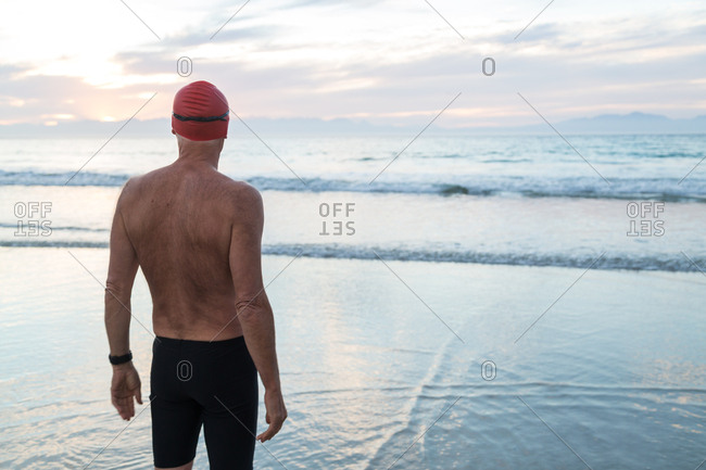 Senior man, aged 65, preparing to swim in the sea at dawn