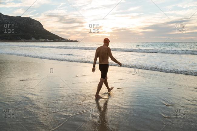 Senior man, aged 65, preparing to swim in the sea at dawn