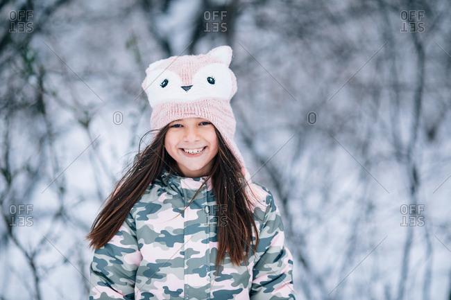 Little girl wearing cute fox knit hat outdoors in winter
