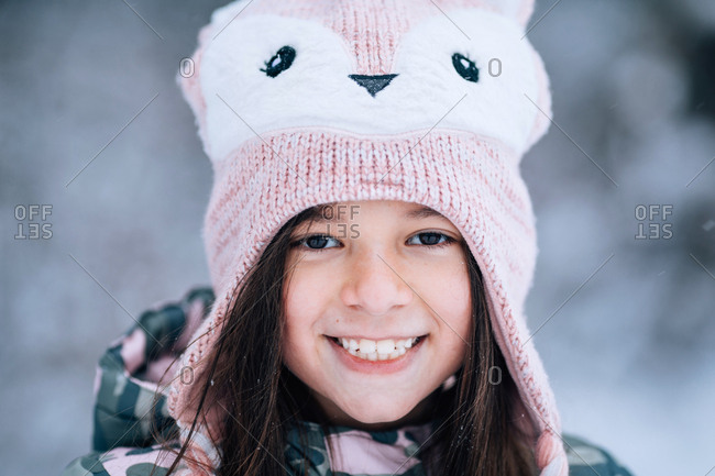 Little girl wearing cute animal knit hat outdoors in winter