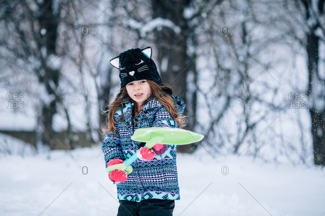 Little girl playing with shovel in the snow