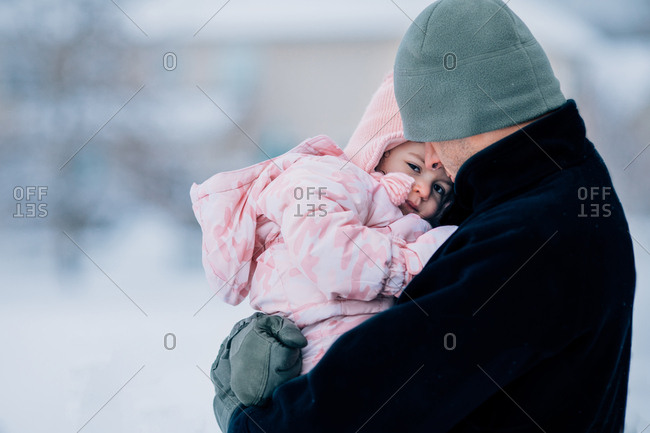 Father holding toddler girl outdoors in winter