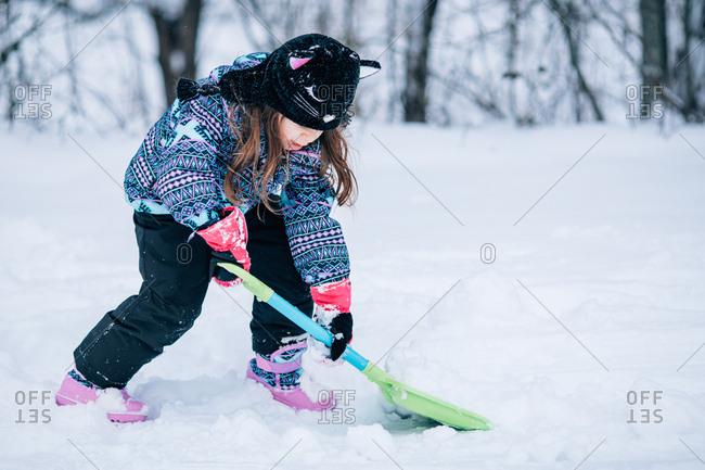 Little girl shoveling snow