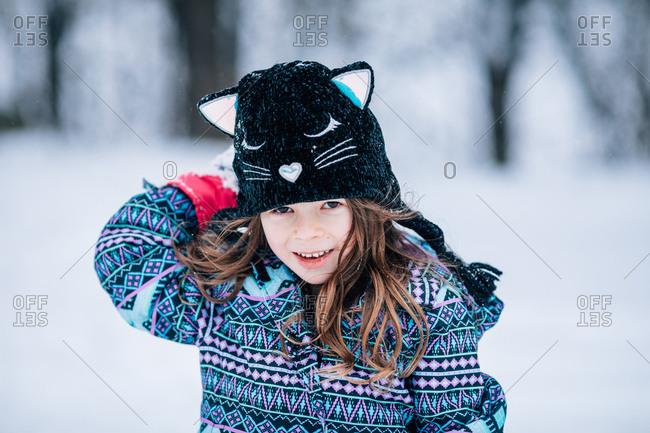 Little girl wearing cute cat knit hat outdoors in winter