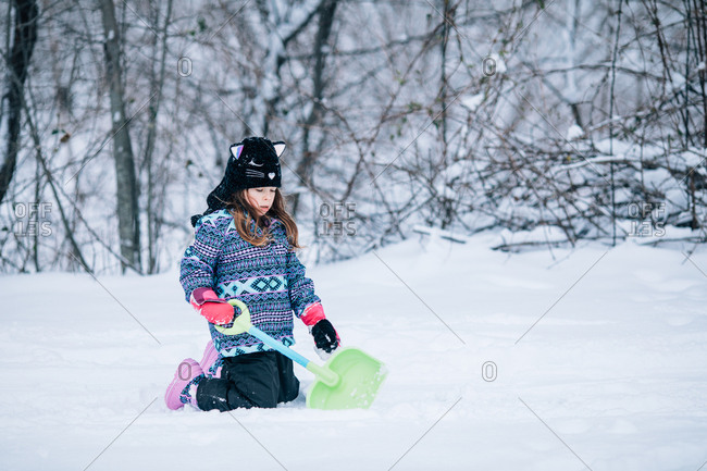 Young girl playing with shovel in the snow