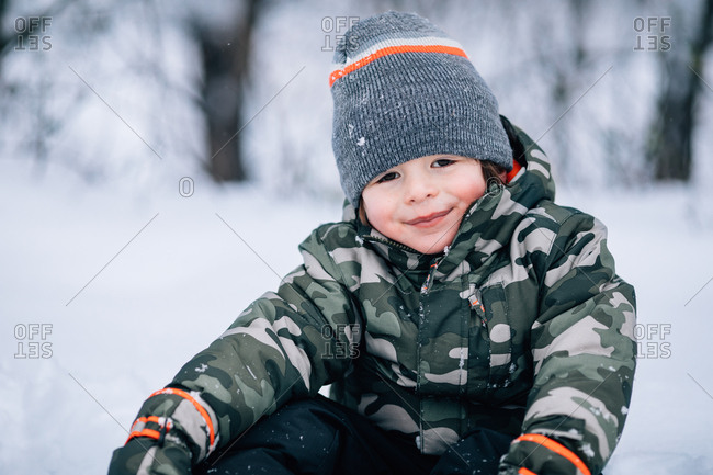 Smiling young boy sitting outdoors in winter