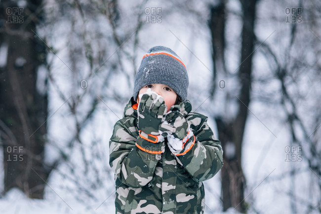 Young boy eating snow