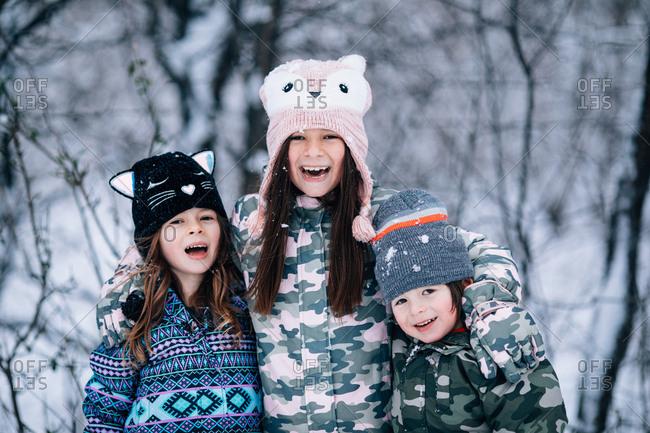 Three happy kids outdoors in winter